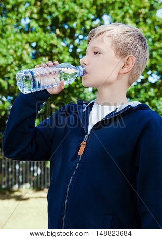 Young teenage boy drinking healthy still water in park summer time
