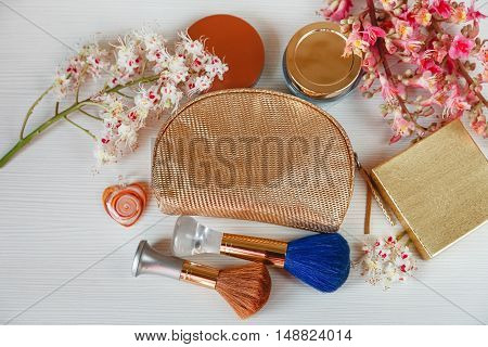 There White and Pink  Branches of Chestnut Tree,Bronze Powder; Two Make Up Brown and  Blue Brushes, Bottle Cream and Gold Box are on White Table,Top View