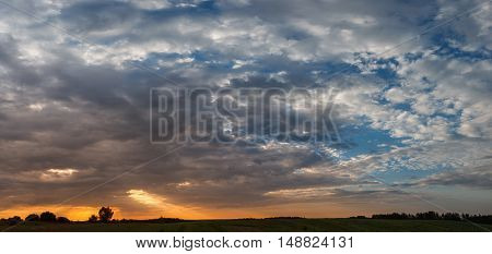 Beautiful dramatic sunset over the field with clouds