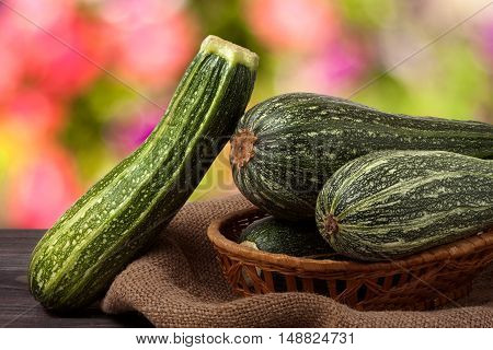 green zucchini on the wooden table with sacking and a blurred background.