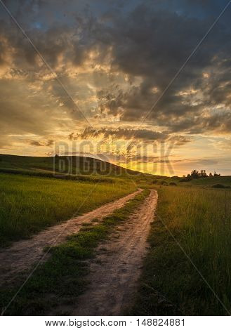 Road in steppe to dramatic sunset, landscape