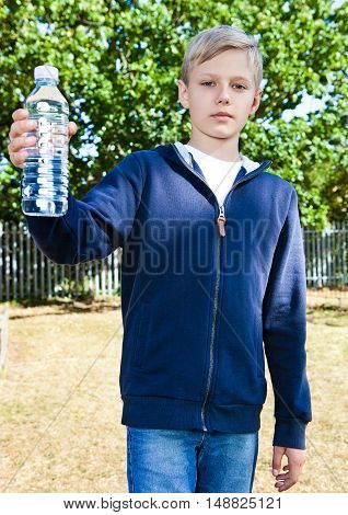 Young teenage boy with bottle of water in park standing on grass