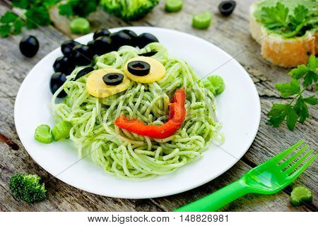 Green monster spaghetti - pasta with green vegetables in the form of funny Frankenstein tasty and healthy dish for children