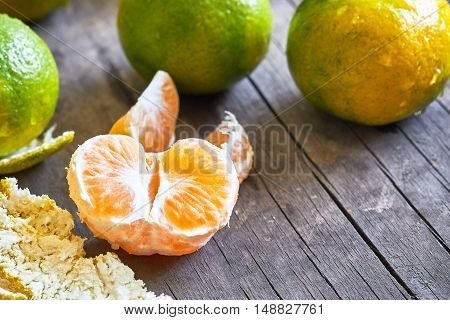 Fresh green peeled tangerine on grey rustic wooden background. Copy space