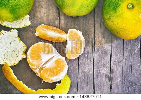 Fresh green peeled tangerine on grey rustic wooden background. Top view with copy space