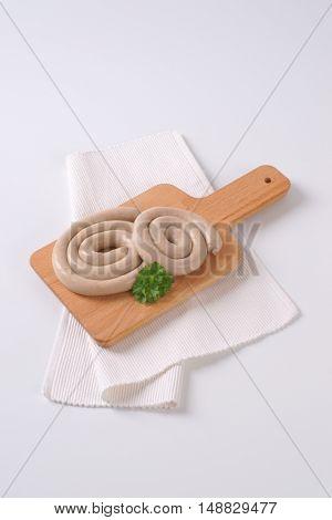 raw spiral pork sausages on wooden cutting board