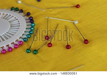 Many sewing push pins on the yellow table