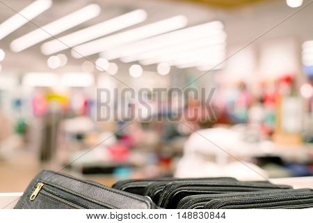 Blured clothing store with selective focus on black purses in the foreground. Defocused background