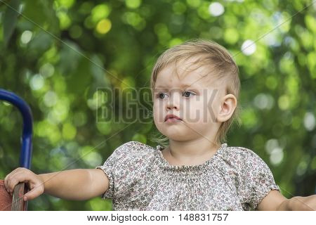 Baby sits on a children's slide. Behind the blurred background of green trees