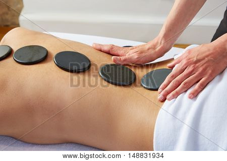 Hot stone massage in woman back with physiotherapist