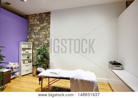 Massage room with massage table and products with stone wall