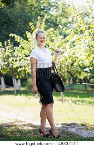 Young beautiful business woman holding a bag outdoors