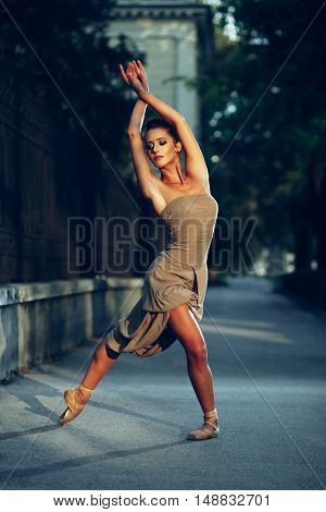 Young beautiful ballerina dancing on the sidewalk
