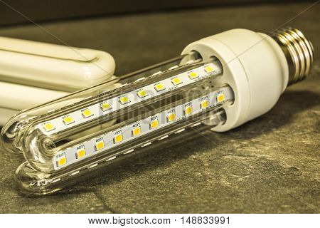 LED bulb in shape similar to a saving CFL bulbs in the foreground of the original CFL bulbs