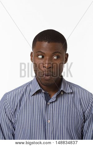 Closeup portrait of surprised Afro-American man posing over white background in studio.Handsome man in blue shirt looking away.