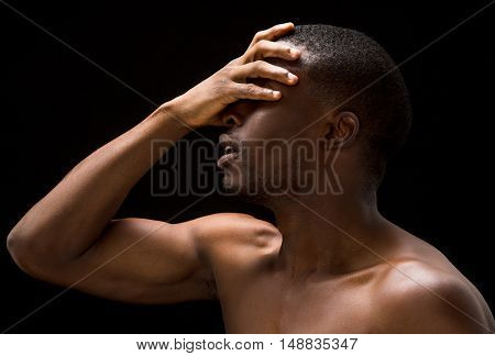 Portrait of naked passionate Afro-American man closing his eyes. Handsome sexy man posing for erotic magazine in studio.