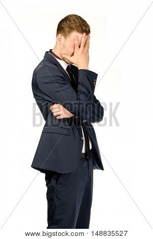 Young businessman in despair covers his face. Crisis concept.