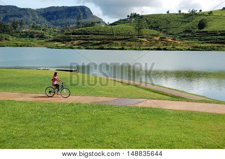 NUWARA ELIYA SRI LANKA - OCTOBER 18 : The girl rides her bicycle near lake in Nuwara Eliya. October 18 2011 in Nuwara Eliya Sri Lanka.