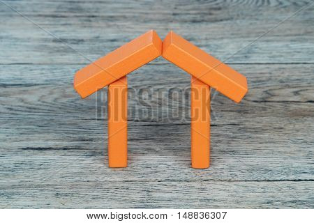 Toy house of orange wooden blocks on old vintage table
