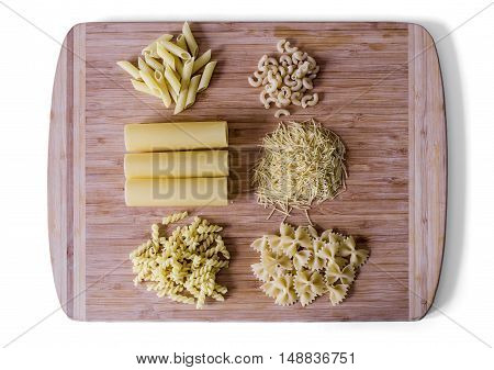 the Italian food - heap of macaroni, spaghetti, noodles, pasta and cannelloni tubes - selective soft focus - clipping path isolated