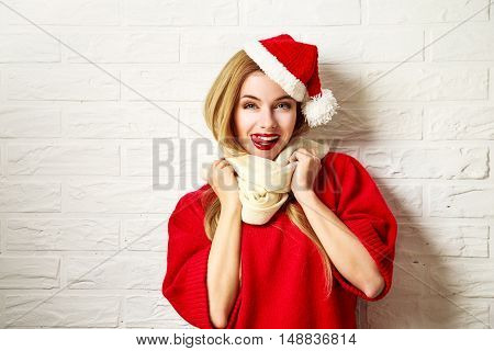 Funny Christmas Girl in Red Winter Clothes Going Crazy at White Brick Wall Background. Winter Woman Fashion Portrait. Toned Photo with Copy Space.