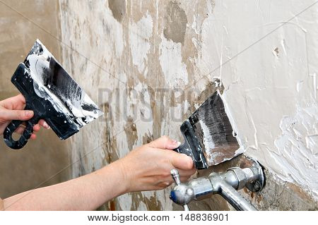 Aligning wall a painters putty painter hands holding stainless steel spatulas close-up.