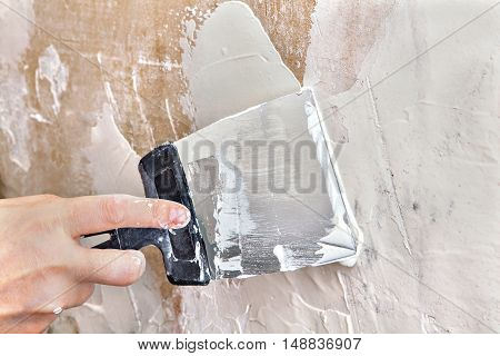 Painting worker puttied wall using a paint spatula hand closeup.