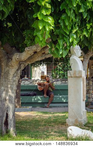 SITIA, CRETE, GREECE - 2016: Street musician is playing guitar on bench in park of Sitia town on Crete island, Greece.