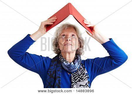 Senior Woman Holding Book Over Head