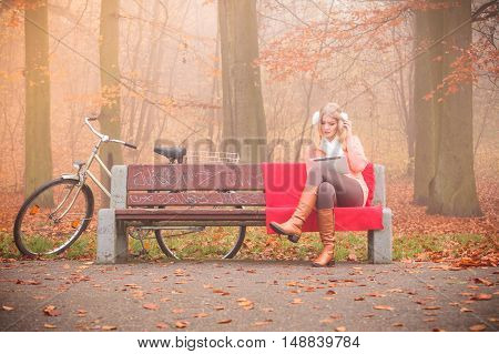 Woodland nature relax cozy fitness internet technology concept. Lady with tablet in park. Young blonde girl sitting on bench browsing websites next to bike.