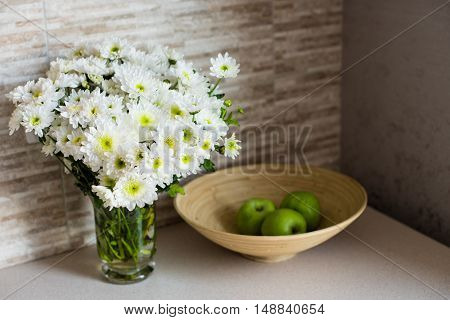 Bouquet of white flowers and apples on a plate in the kitchen interior