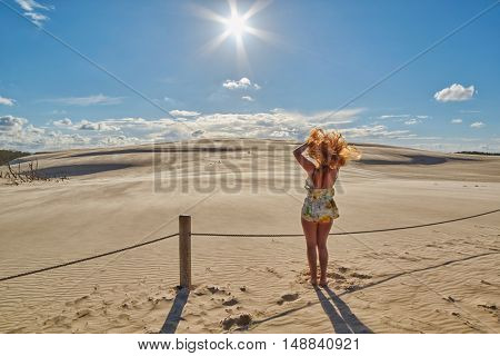 Happy Young Redhead Woman with curly hair waving hands against Sunset at Sand Dunes in Leba, Poland