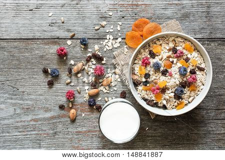 breakfast with muesli berries nuts and dried fruits on rustic wooden background. top view