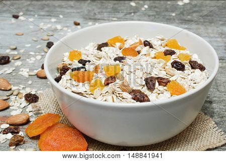 bowl of muesli with dry fruits and nuts on rustic wooden background. close up
