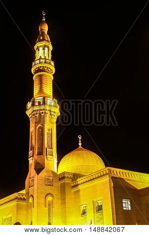 The Minaret and dome of Jumeirah Mosque illuminated at night in Jumeirah Beach, Dubai, UAE. The Jumeirah Mosque is one of the symbols of Dubai and is the only religious monument open to non-Muslims.