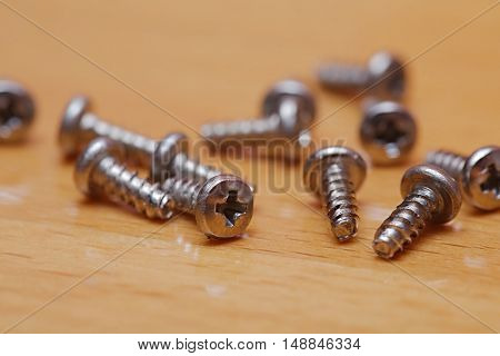 Tiny screws on a wooden table