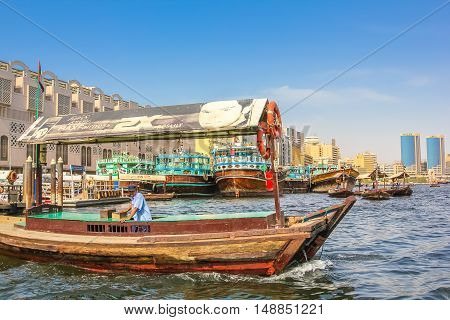 Dubai, United Arab Emirates - May 3, 2013: close up of traditional wooden boat docked on the Bay Creek in United Arab Emirates. On background, skyline of Deira, the old downtown of Dubai.