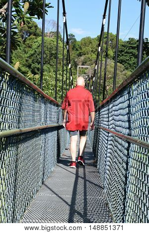 A rear view of a lonely man walking along a bridge
