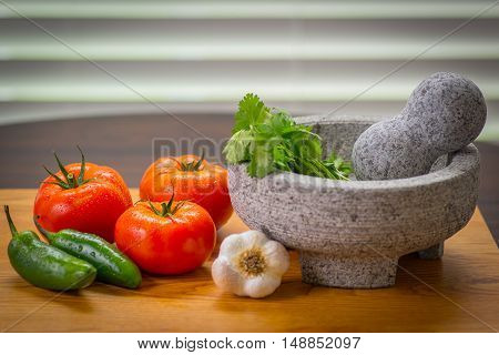 Zesty salsa with chips, tomato and peppers, pico de gallo molcajete (mortar) and tejolete (pestle)