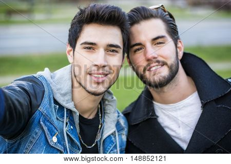 Two young men taking selfie while outdoors, point of view of the camera itself