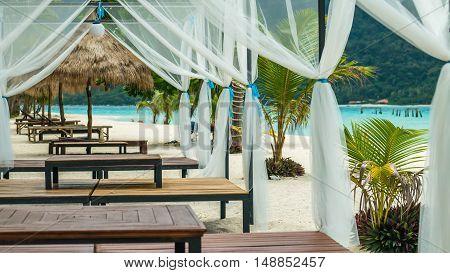 Beach bed on white sand among palm trees in full sun, Koh Lipe, Thailand