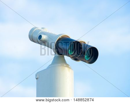 Stationary binocular against clear blue sky. Front view with reflection in the lens