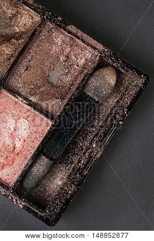 Crushed used eyeshadow in compact box with applicator covered by eyeshadow dust. On black cardboard background. Top view
