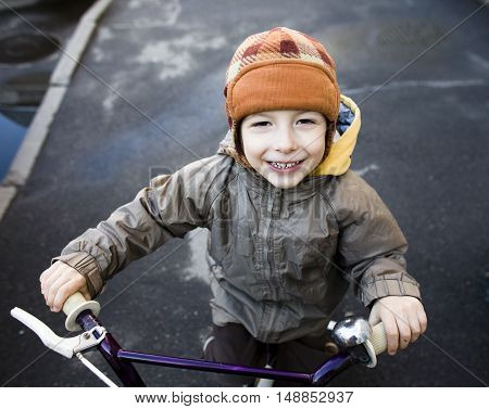 little cute real boy on bicycle smiling close up emotional posing