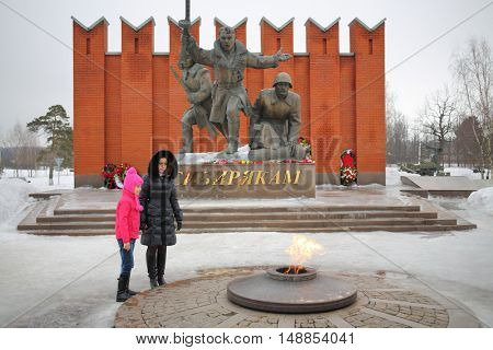 MOSCOW - FEB 23, 2015: Mother and daughter (model release) are near the eternal flame at the memorial complex of Siberian soldiers