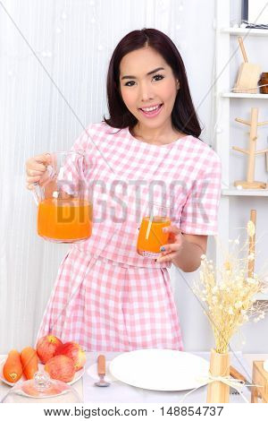 Healthy woman standing in front of dining table has pitchers and a glass of juice in her hand.