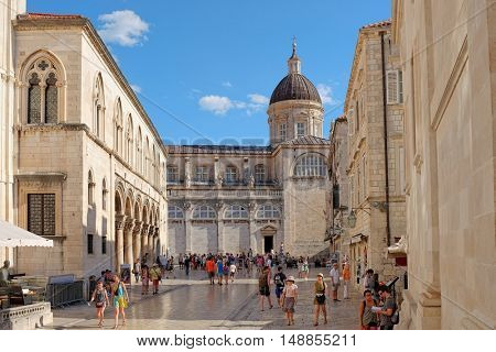 DUBROVNIK OLD TOWN, CROATIA - JULY 20, 2016: street crowded of tourists, on background the dome of the Assumption Cathedral