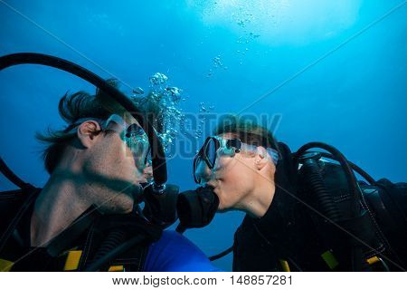 Couple of scuba divers kissing each other underwater