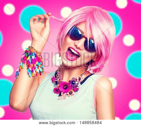 Beauty teenage model girl with pink hair, fashion colorful accessories and sunglasses over bright polka dots colourful background, Joyful young woman with short haircut laughing