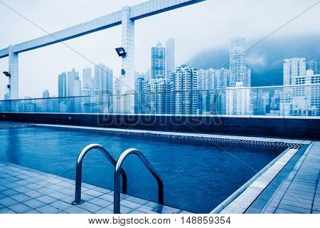 swimming pool at roof with hong kong residential apartments background,china.